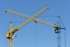 Two building crane yellow and blue visually inters. Two crane yellow and blue visually intersect. Depicted against the blue, clear sky Royalty Free Stock Photos