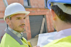 Two building designers chatting on site inside Stock Images