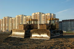 Two bulldozers in morning. At buildings buckground Stock Photography