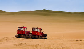 Two bulldozers working in desert Stock Images