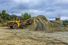 two bulldozers working on a quarry, rain clouds in the background stock image