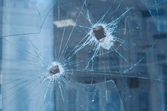 Two bullet holes in the glass windows Stock Images