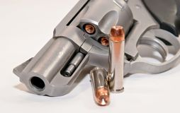Two bullets in front of a loaded revolver. A .357 magnum revolver loaded with hollow point bullets with two shown next to the gun with a white background stock image