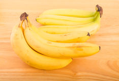 Two Bunches Bananas. A bunch of yellow, ripe bananas on a wood table Royalty Free Stock Photo