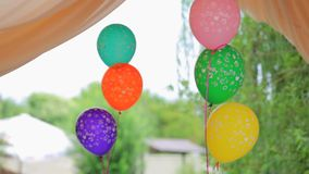Two Bunches Of Colorful Balloons Swaying On Wind. CLOSE UP. This is a shot of two bunches of multicolored balloons with a word BABY linked by tape slightly stock video