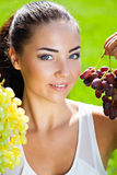 Two bunches of grapes in hands of young woman Stock Photos