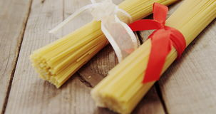 Two bundles of spaghetti pasta toed up with ribbons. On wooden table stock video