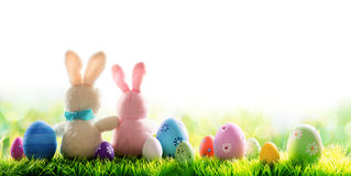 Two Bunnies With Decorated Eggs Isolated On Sunny Meadow stock photo