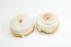 Two buns with icing and cinnamon isolated on white Stock Photos