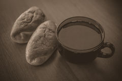 Two buns and large cup of tea on wooden table in a vintage tone Royalty Free Stock Image
