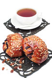 Two buns with raisins and sunflower seeds and cup of tea Royalty Free Stock Photo