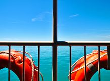 Two buoys white metal railings sea and sky. View from ship, two buoys lifesavers and white metal railings. Summer day deep blue sky and sea contrasts with white royalty free stock photo