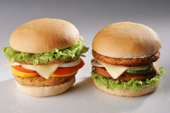 Two burgers. A chicken cheese burgers and a beef cheese burgers Royalty Free Stock Images