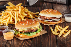 Two burgers with grilled meat with french fries on craft paper o Royalty Free Stock Image