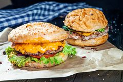 Two burgers with meat, spices and sauce on a craft paper on a black wooden background. royalty free stock images