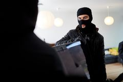 Two burglars steal TV from home. Two burglars steal a big TV from the living room of a house stock photography