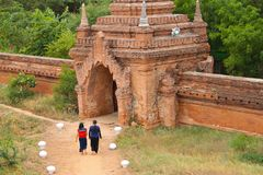 Two Burmese girls walking towards a temple in Bagan, Myanmar Burma. Two Burmese girls walking barefoot towards a temple in Bagan, Myanmar Burman royalty free stock photography