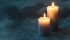 Two burning candles on navy blue background. Close up stock photography