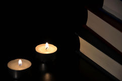 Two burning candles. And old book in the dark Royalty Free Stock Photography