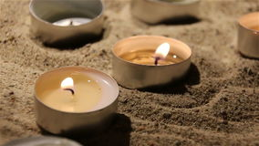 Two burning candles in the sand in church.  stock video footage