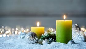 Two Christmas candles on snow stock photos
