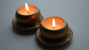 Two burning decorative candles in gold color. On a light background stock footage