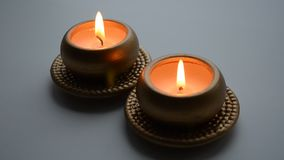 Two burning decorative candles in gold color. On a light background stock video footage