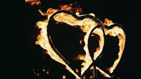 Two burning heart at night. Two burning heart. Fire show on the street at night stock video footage