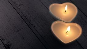 Two Burning Heart Shape Candles. Two heart candles on wooden table top stock footage