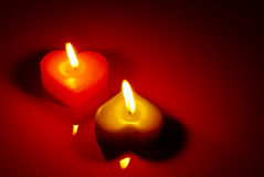 Two burning heart shaped candle Stock Images