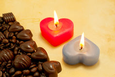 Two burning heart shaped candles and candies Royalty Free Stock Photos