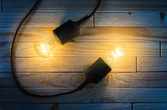 Two burning bulbs on a wooden background stock photography