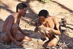 Two bushmen hunters kindle a fire Royalty Free Stock Photos