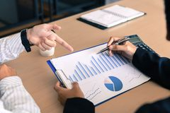 Two business asian man anaysis chart summary report and pointing on paperwork royalty free stock photo