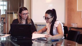 Two business women wearing glasses in business clothes discussing a business project in an office sitting at a table. Two business beautiful business women stock video