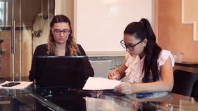 Two business women wearing glasses in business clothes working on a business project in an office sitting at a table. Two business beautiful business women stock footage