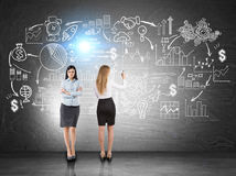 Two business coaches, planning, blackboard. Rear view of a blonde businesswoman wearing a white blouse and a skirt and drawing a business sketch on a blackboard stock photos