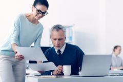 Two business colleagues comparing documents at work stock images