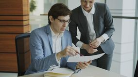 Two business colleagues discussing reports in modern office. Businessman sitting at the table talking his female partner. Two business colleagues discussing stock footage