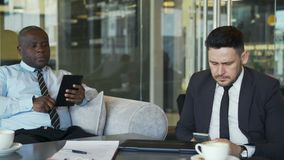 Two business colleagues in formal wear sitting and using their smartphone and tablet in glassy cafe during meeting. Two multiracial business colleagues in formal stock video