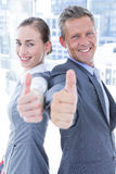 Two business colleagues giving thumbs up Stock Images