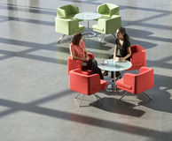 Two business colleagues having a meeting over a hot drink in an office building Royalty Free Stock Image