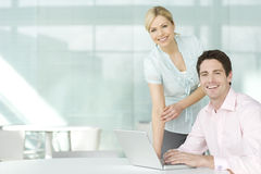 Two business colleagues at a laptop, smiling royalty free stock images