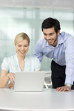 Two business colleagues looking at laptop, smiling royalty free stock photos