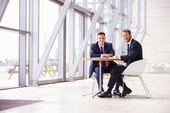 Two business colleagues in modern interior, looking to camera Royalty Free Stock Photo