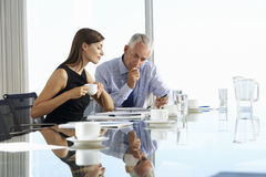 Two Business Colleagues Sitting Around Boardroom Table Having In Stock Photo