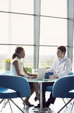 Two business colleagues sitting at a table, having a meeting Royalty Free Stock Images