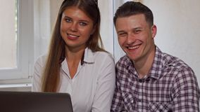 Two business colleagues smiling to the camera, while using laptop stock images