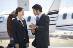 Two business colleagues standing by a plane stock image