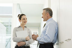 Two business colleagues talking in corridor Stock Images